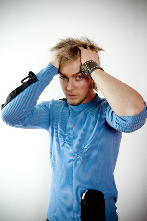 20 year old: Portrait of a 20 year old man with his hands in his hair on top of his head. Troubled man Stock Photo