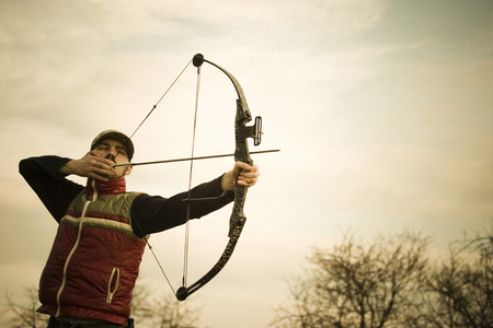 poised: Man poised to release an arrow from a bow.