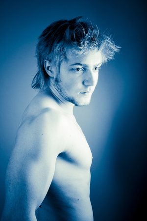 A profile portrait of a shirtless, muscular young man looking over his right shoulder, digitally colored in a blue tint.