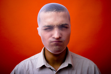 Angry young man with his head covered by a transparent stocking. Isolated on orange background, horizontal format.
