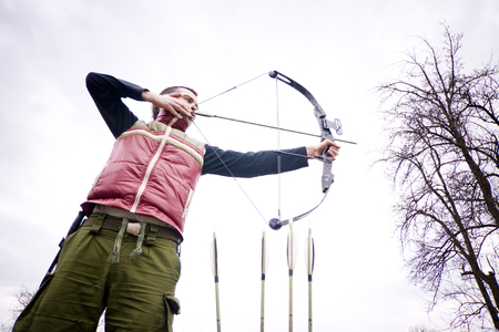Man with bow and arrow taking aim.