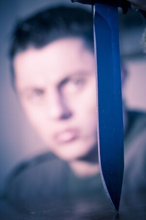 crazed: Blurred face of an angry man contemplating a knife. Stock Photo