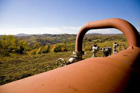Large commercial pipeline shown in rural countryside setting at a point where it is above ground. Stock Photo