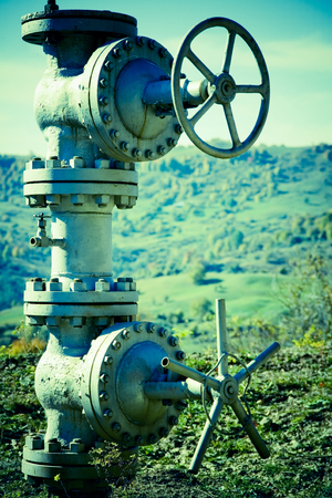 Closeup view of piping and valves that protrude above ground in a rural, hilly countryside and are connected to an underground commercial pipeline . Stock Photo