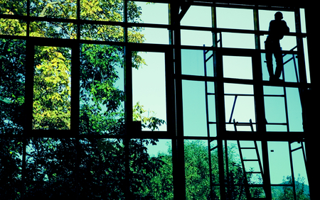 downtime: Silhouette of resting worker through large windows. Stock Photo