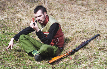 sitting on the ground: A view of a hunter sitting cross-legged on the ground, inspecting a shotgun shell with his rifle laying on the ground beside him.