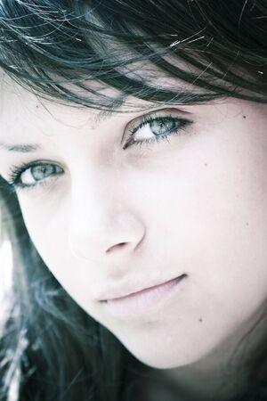 discreto: Morena chica adolescente hermosa con discreta sonrisa serena; retroiluminada. Foto de archivo