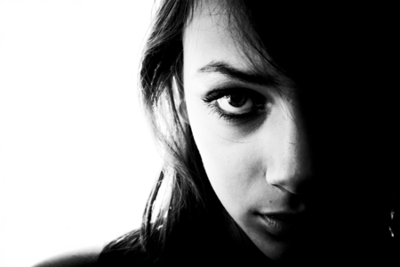 tentative: Black and white portrait in horizontal form of a mysterious looking teen girl, one side of her face in shadows.