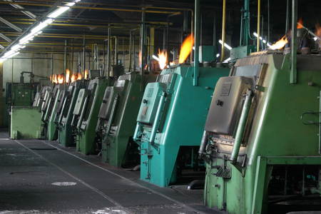 machines: Factory scene with lined up industrial machines blowing flames, metallurgic industry .
