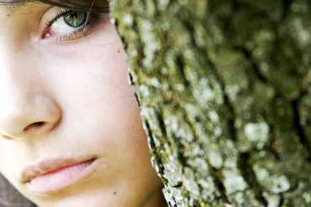 face in tree bark: An enigmatic girl with green eyes looking sideways to the camera, her face partly obscured by a green tree bark that matches her eye. Stock Photo