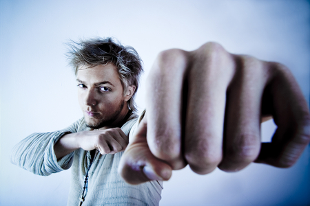 distressing: Aggressive young man violently strikes out with a clenched fist.
