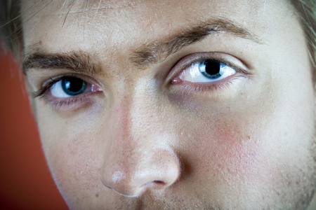 Closeup of a 21 year old mans face with with emphasis on his blue eyes. Stock Photo
