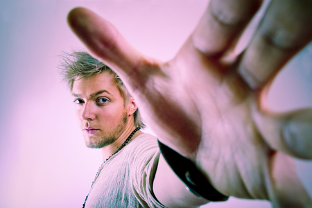 outstretched hand: Nervous male in aggressive stance with outstretched hand at reach of camera. Stock Photo