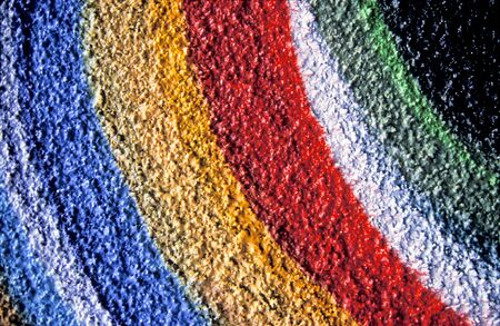 Abstract closeup shot of a graffiti wall with painted rainbow texture.
