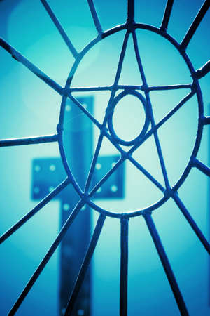 A welded metal star grill with circular rays in the foreground and a cross with holes in the background. Silhouettes with bluish tones. Stock Photo