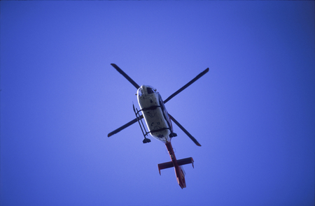 A upward view of a flying helicopter, its rotor blades frozen in action. Centred in the image frame.