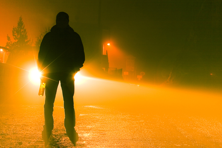 inebriated: A silhouette of a drunk person standing on the road on a foggy night holding a bottle. Stock Photo