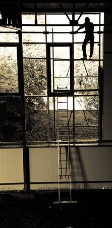 silhoutted: Construction worker climbing on scaffolding. Image is sepia toned, figure of the construction worker is silhoutted. Stock Photo