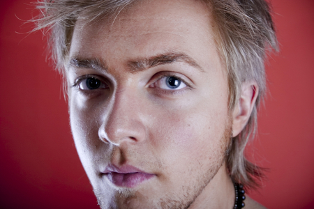 20 year old: Closeup of the serious face of a 20 year old man with blond hair and blue eyes.