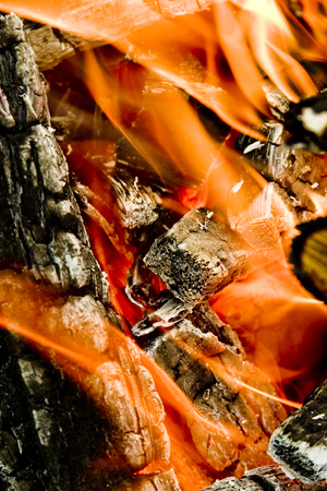 A view into the middle of a wood fire with flames, glowing embers and blackened wood logs with white ashes.