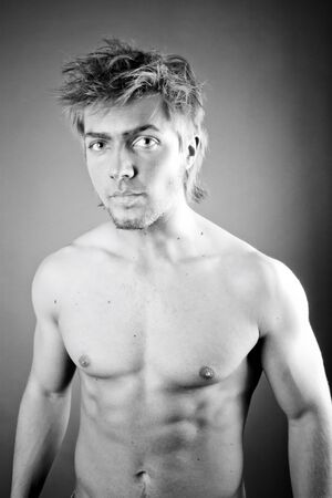 brawny: Black and white portrait of a shirtless 21 year old man with a serious expression. Isolated on background.