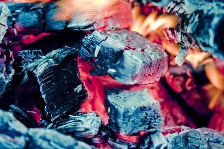 ablaze: A close up of a coal fire, with the black charcoal engulfed by orange flames. Stock Photo