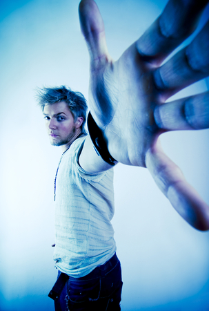outstretched hand: Man with outstretched hand reaching for camera in aggressive pose.