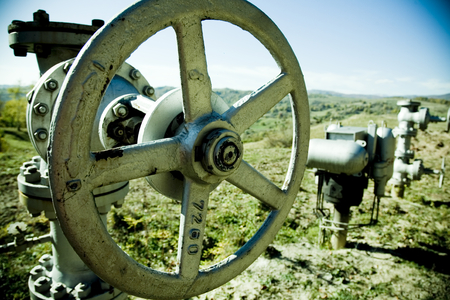 Industrial pumps and valves that protrude above an underground pipeline in a rural, countryside setting.