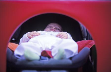 slumbering: Baby sleeping in crib or stroller; red background