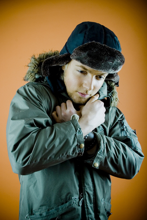 Portrait of a 21 year old man with a winter coat and hat on, holding the coat closer together at the neck to keep warm. Distant expression. Isolated on orange background, taken in studio. Stock Photo