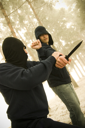 protects: A young armed male protects himself from a mugger.