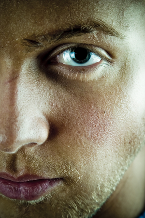 reflective: Closeup of a 20 year old mans face with with emphasis on one eye and the left side of his face.