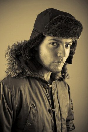 Male model dressed in parka and Ushanka hat. Vertical orientation, and sepia-toned. Stock Photo
