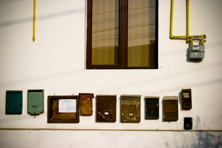 meter box: Row of assorted mail boxes on the wall of a building. Window and meter also visible.