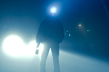 Car lights. silhouette of a man with a wine bottle in one hand and a search light on his head. Stock Photo
