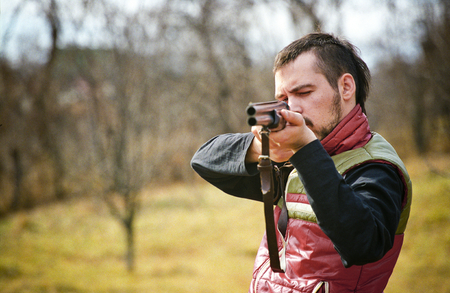 squint: A young hunter taking aim with his rifle.