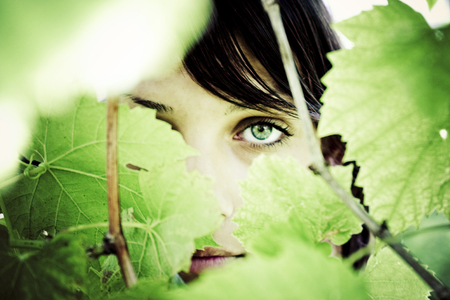 mystery woman: Mystery woman behind the cover of some leaves. Stock Photo