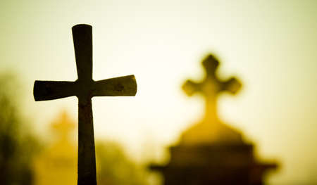 headstone: A picture of a simple cross in the foreground and another cross atop a headstone in the distance.