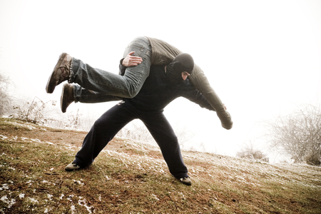 aggressiveness: Karate training outdoors, two men fighting.