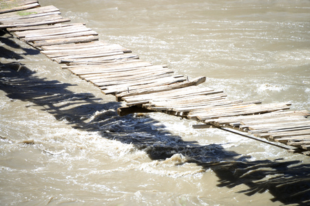 Wooden bridge over beautiful and wild Bartang River near Siponj, Pamir Mountain Range, Tajikistan