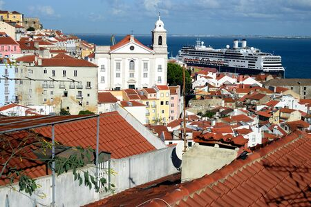 Cruise ship in Lisbon harbor and traditional red roofs of Alfama district. Portugal