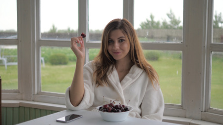 Cute girl in a white coat, sitting on the veranda and eating cherry.