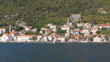 Sailing In Boka Kotor Bay Near Old Town With Stone Houses And Roofs Of Red Tiles Stok Fotoğraf