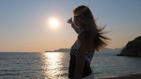 Pleasure Female Hands Catch The Sun In The Sky Standing On Coast Sea