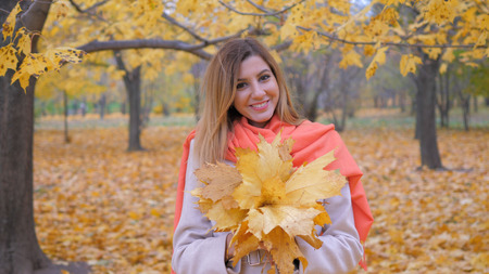Cute Lady In Beige Coat And Orange Scarf Holding Bouquet Yellow Autumn Leaves