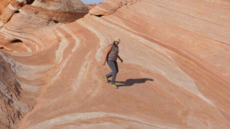 Tourist Woman Descends From The Top Of The Hill On The Colored Stone Red Rocks