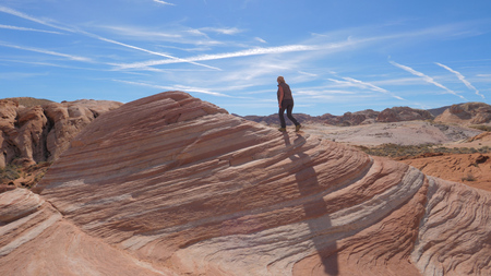 Sports Hiking Woman Climbs Up The Red Rock Background The Sky