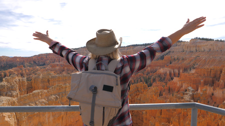 Woman Raised Hands Upwards While Standing On Observation Deck Overlooking Canyon