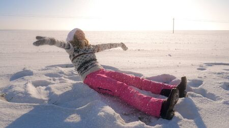 Playful young woman in a warm sweater and pink pants sitting in a winter field. Throws snow up then falling snowflakes to her. Enjoys outdoors. At sunset.