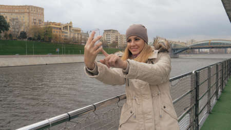 Woman Selfie On Smartphone Standing On The Embankment Of River And City Views